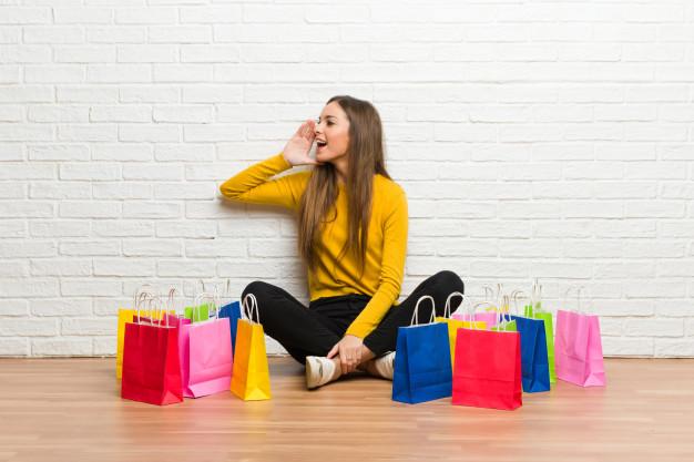 Mulher sentada no chão rodeada de sacolas de compra