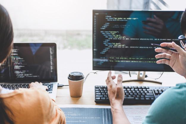 Imagem de duas pessoas conversando em frente a dois computadores com copos de café na mesa e os computadores ligados e com linhas de códigos aparecendo