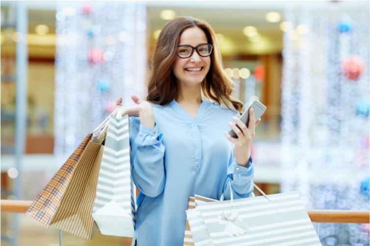 Imagem de uma mulher segurando sacolas de compras e sorrindo para a foto, ela veste uma roupa e o fundo da foto é de um shopping em tons de azul