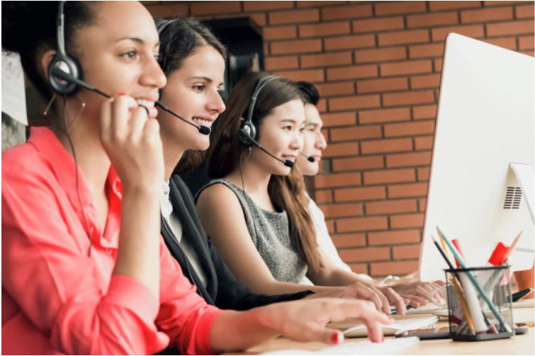 Imagem de três moças que com fones e microfones falando com clientes