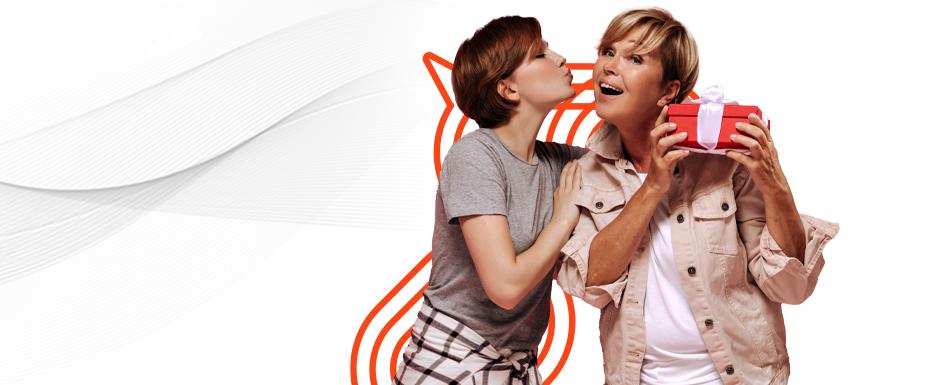 Filha presenteando a mãe em quanto a beija no rosto aproveitando as ofertas dos e-commerces que souberam o que fazer para vender no dia das mães.