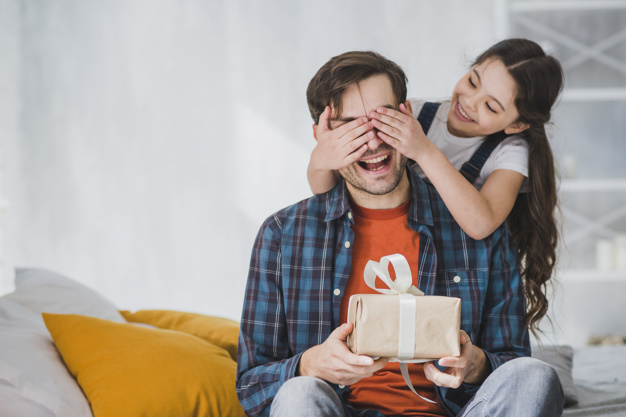 fathers-day-concept-with-daughter-covering-fathers-eyes_23-2147805571