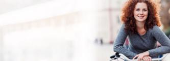 mulher apoiada em uma bicicleta