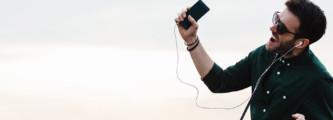 homem escutando música no celular e cantando
