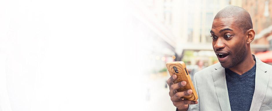 homem olhando celular surpreso