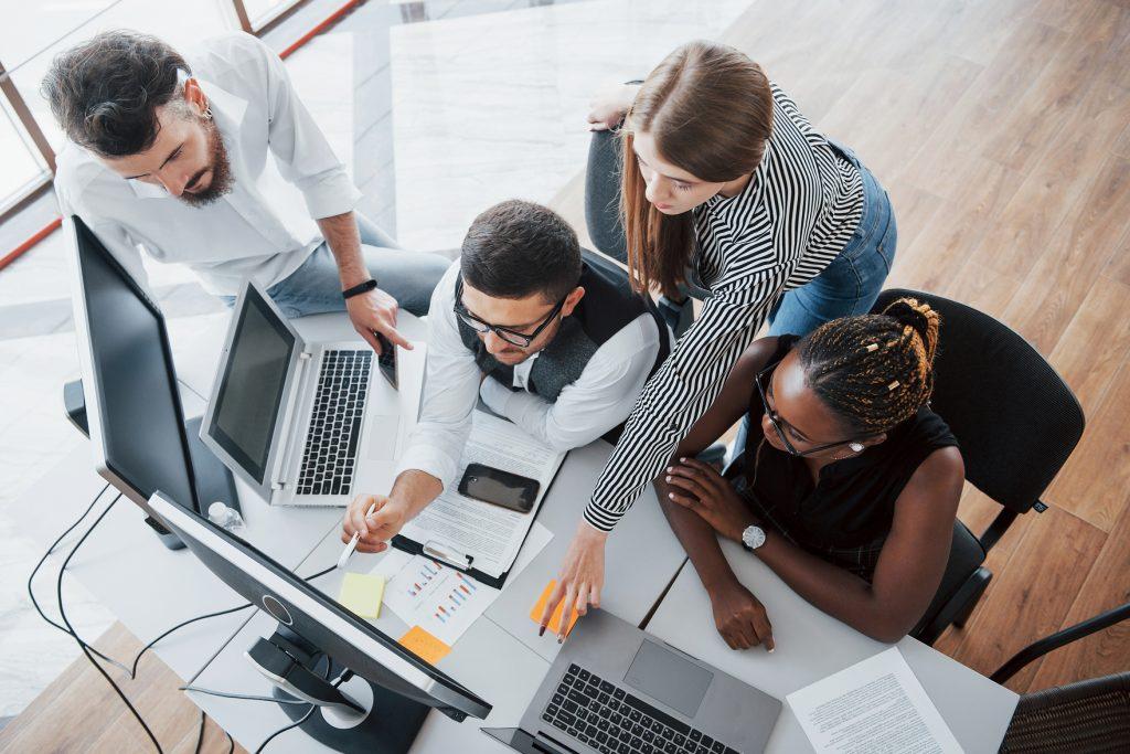Imagem de uma equipe de planejamento de vendas sentada à mesa, na frente e computadores. A equipe é composta por dois homens e duas mulheres
