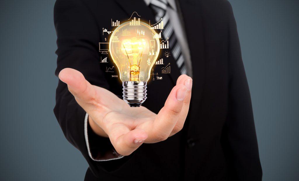 Imagem de uma mão segurando uma lâmpada acesa