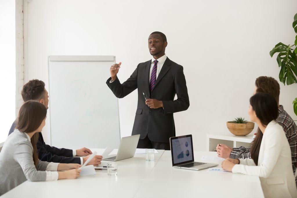 Imagem de um chefe em uma reunião com seus colaboradores. Ele está de pé na frente de uma parede branca e as outras pessoas sentadas à mesa