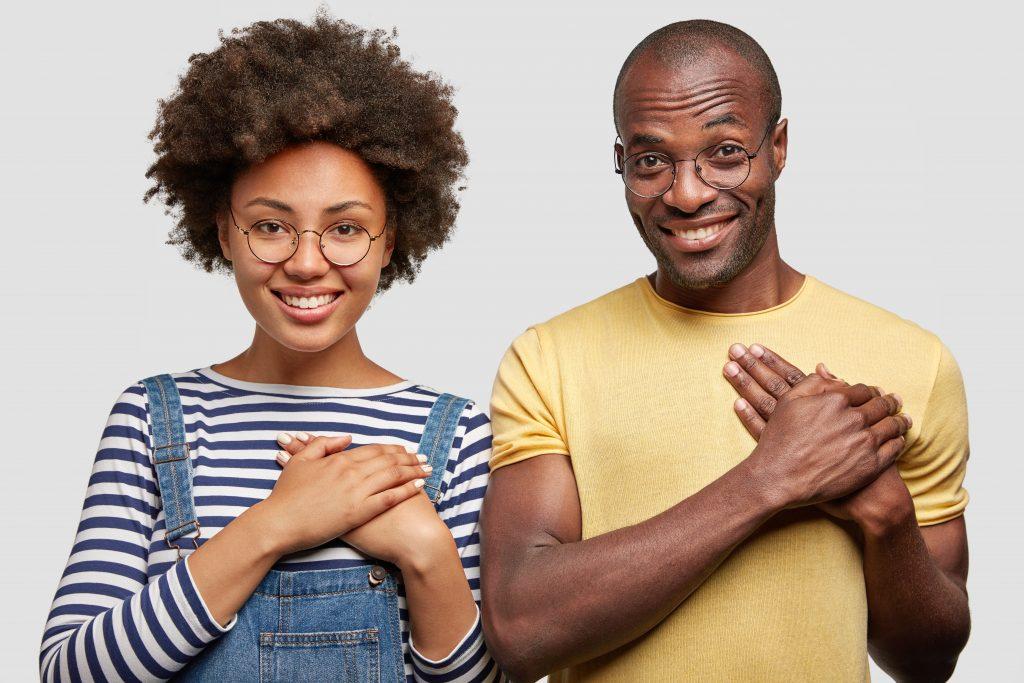 Imagem de uma mulher e um homem negros, lado a lado, com as mãos em formato de concha encostada no lado esquerdo do peito em alusão ao coração e como funciona um programa de fidelidade