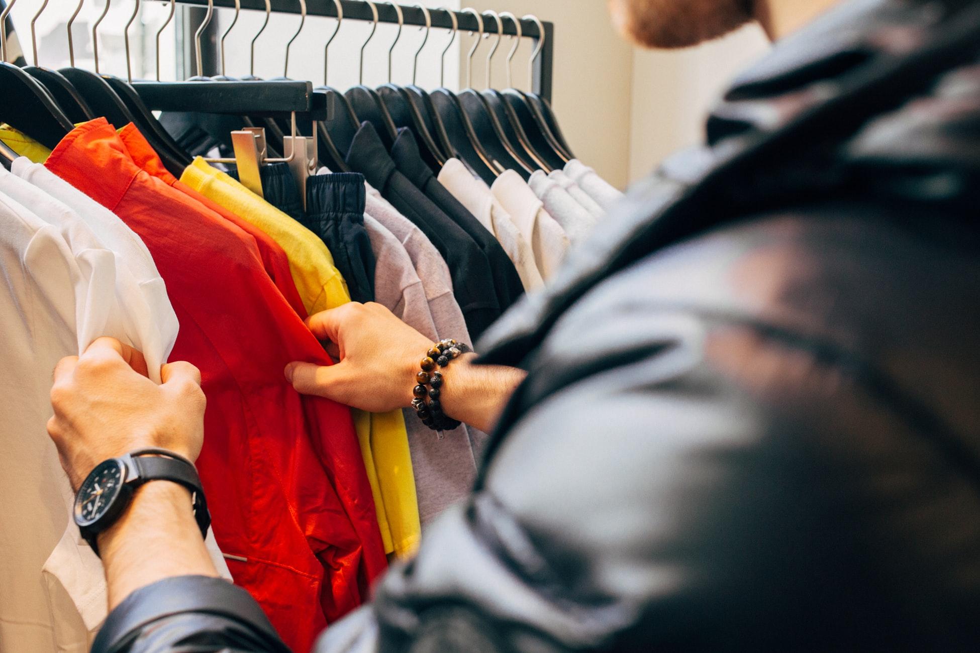 homem procurando roupas em uma arara na black friday