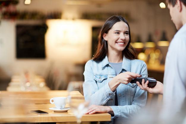 A imagem apresenta uma cliente sorrindo ao ser bem atendida em um estabelecimento.