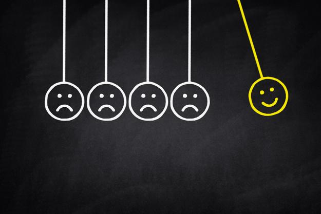 Para representar o NPS, ou net promoter score, a imagem apresenta um pêndulo de newton, em que a bolinha que balança é um rosto feliz e as demais bolinhas que serão acertadas pelo rosto feliz, são rostos tristes.
