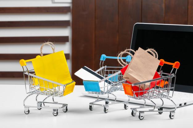 Para representar o NPS, a imagem apresenta carrinhos de compra em miniatura ao lado de um computador.