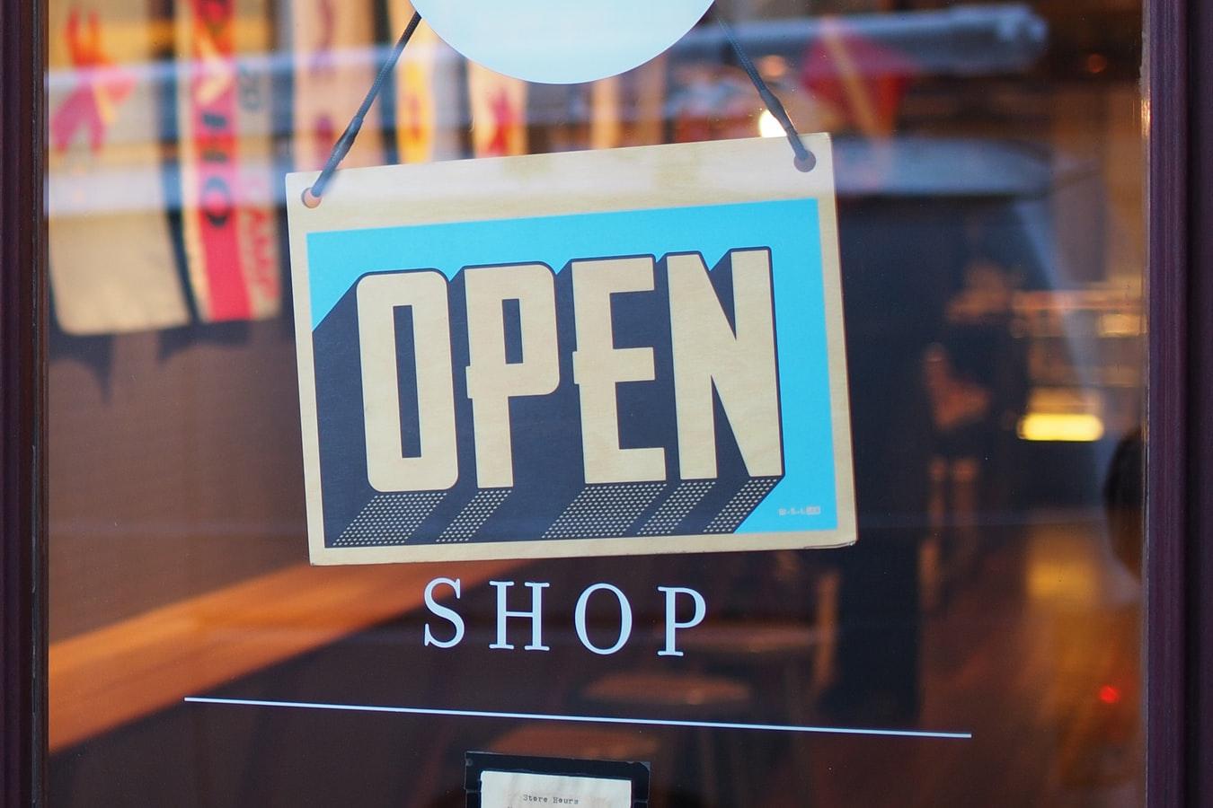"""Porta de um estabelecimento com uma placa """"open"""""""