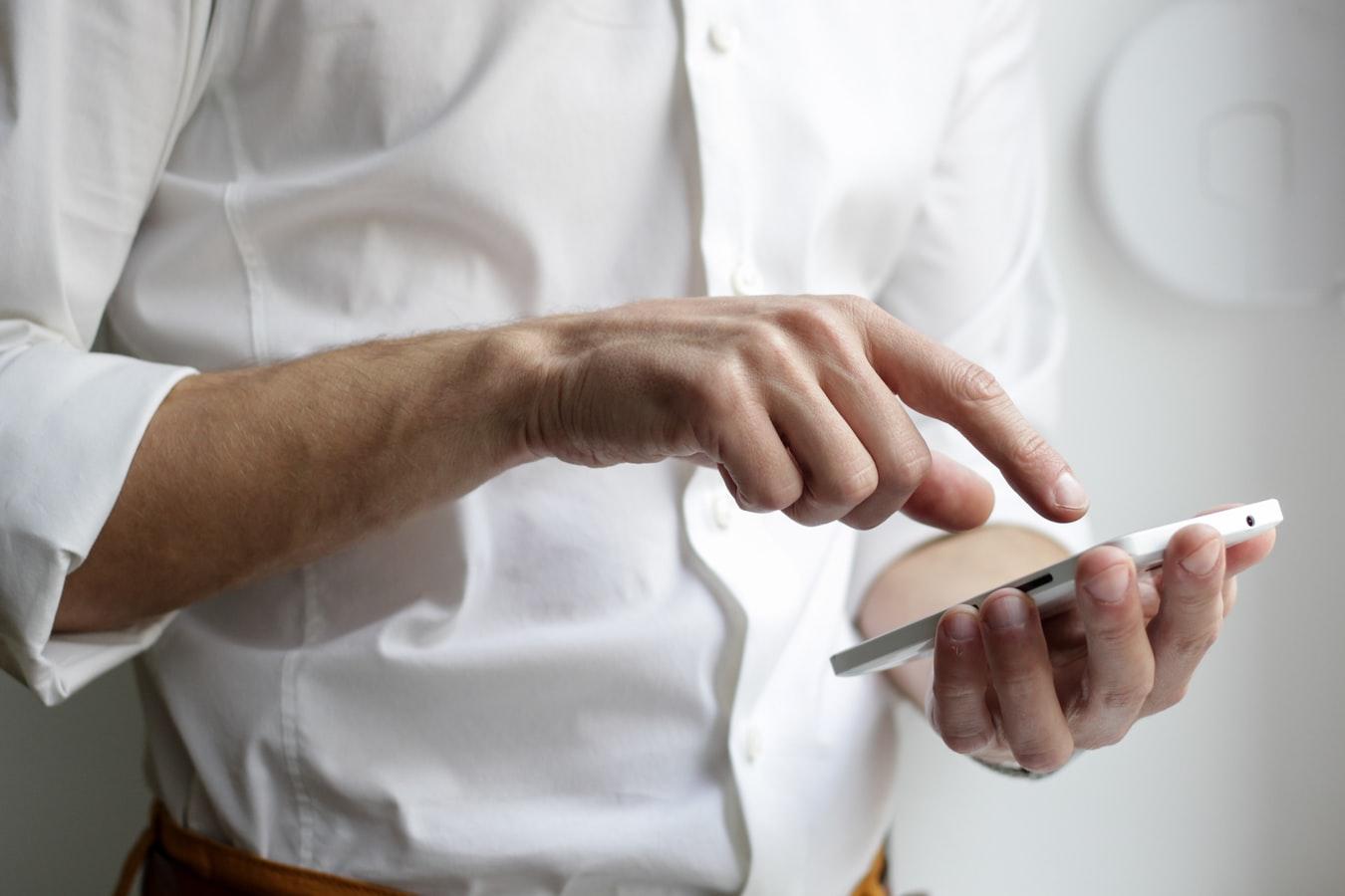 Para representar o mobile marketing, a imagem apresenta uma pessoa segurando seu smartphone, acessando aplicativos.