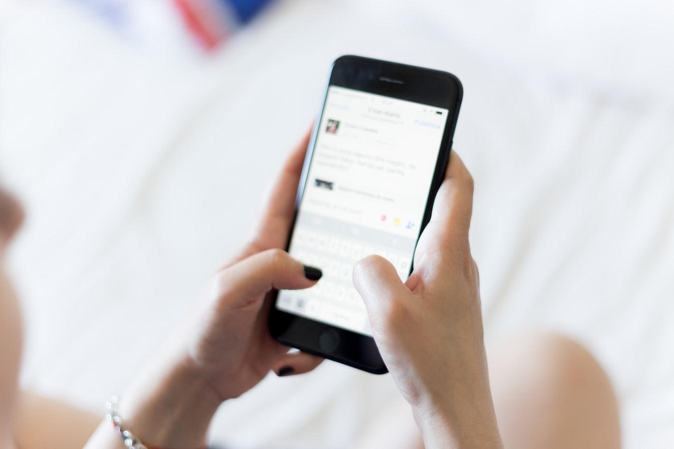 Uma usuária de smartphone acessando as redes sociais, sendo impactada pelo mobile marketing.