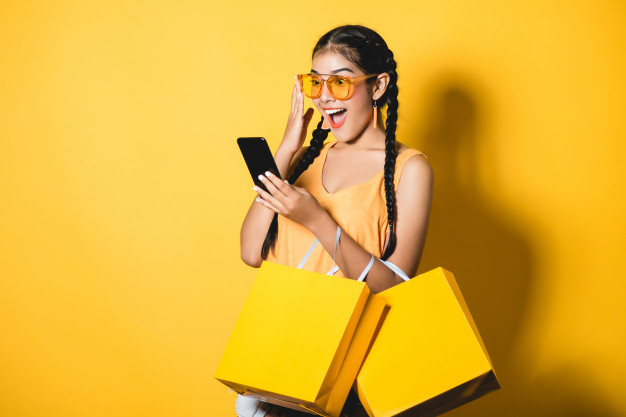 Uma mulher com sacolas de compras vendo promoções do dia do consumidor em seu smartphone.