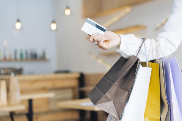 Um cliente com seu cartão de crédito e várias sacolas de compras aproveitando o dia do consumidor.