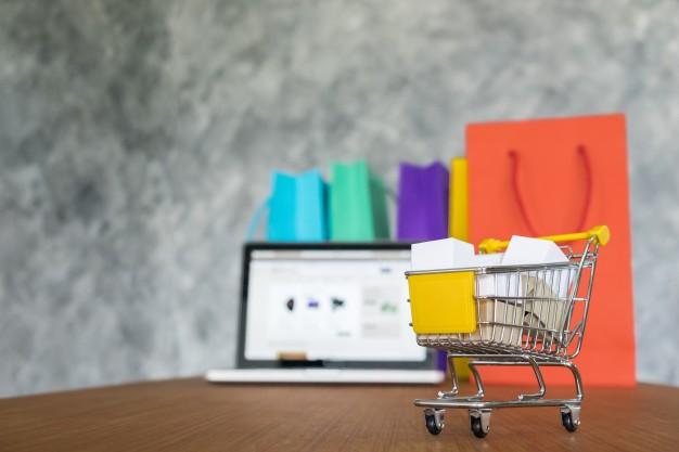 A imagem apresenta um carrinho de compras em miniatura, com sacolas de compras e um notebook em um e-commerce no dia do consumidor.