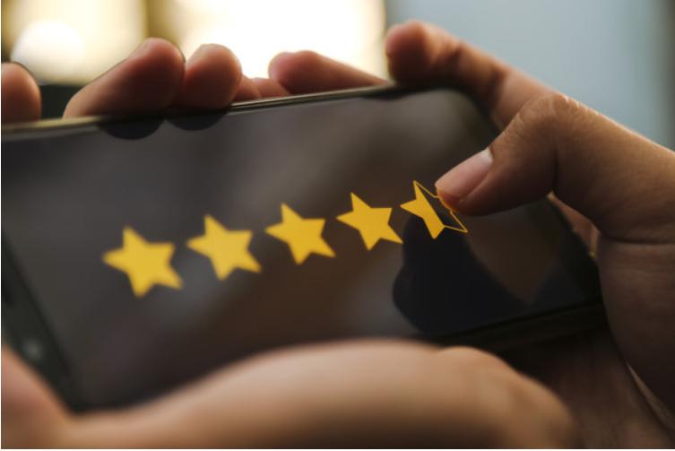 Imagem de uma pessoa com o celular deitado apertando cinco estrelas para canais de comunicação