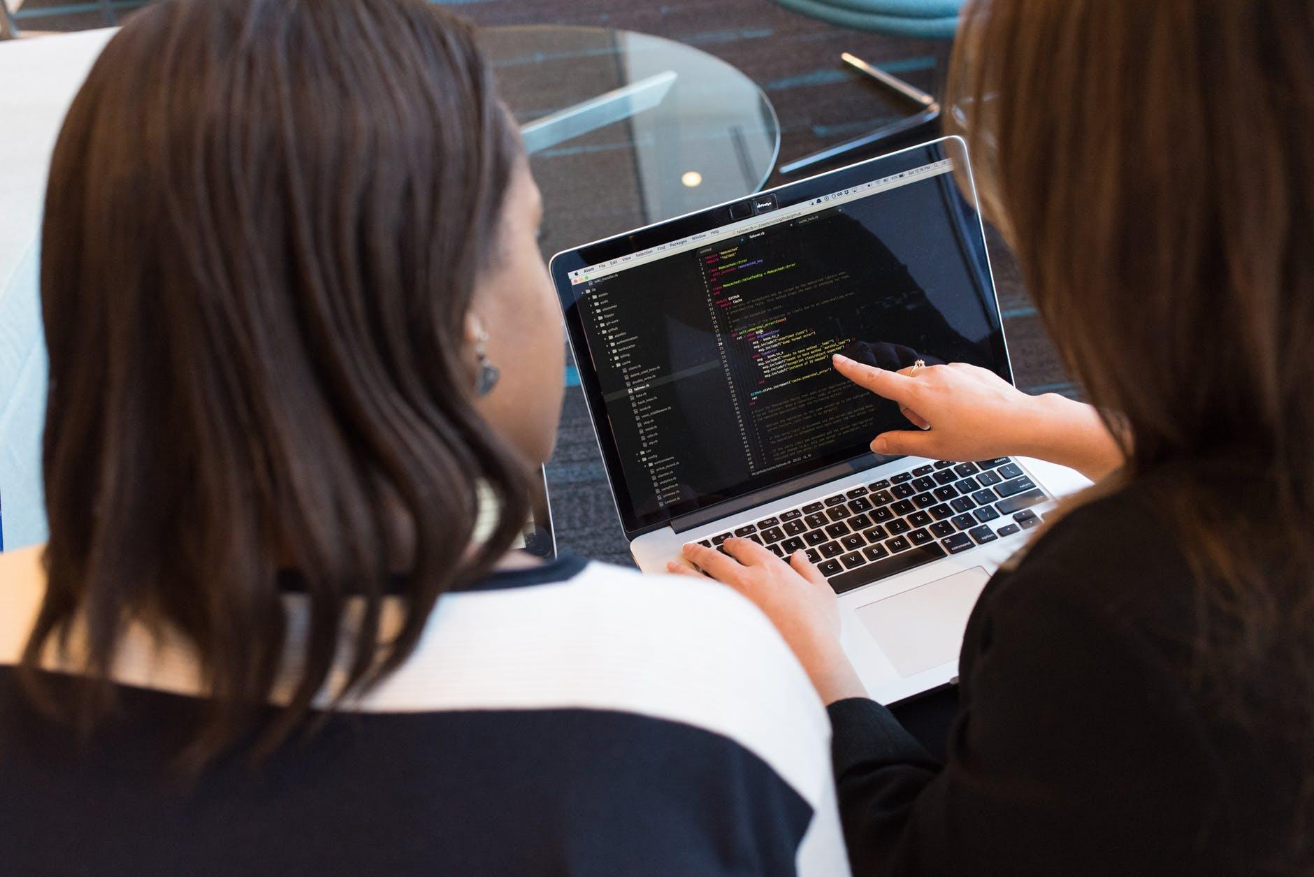 Imagem de duas mulheres conversando sobre dados estruturados na frente de um notebook ligado e com linhas de código na tela