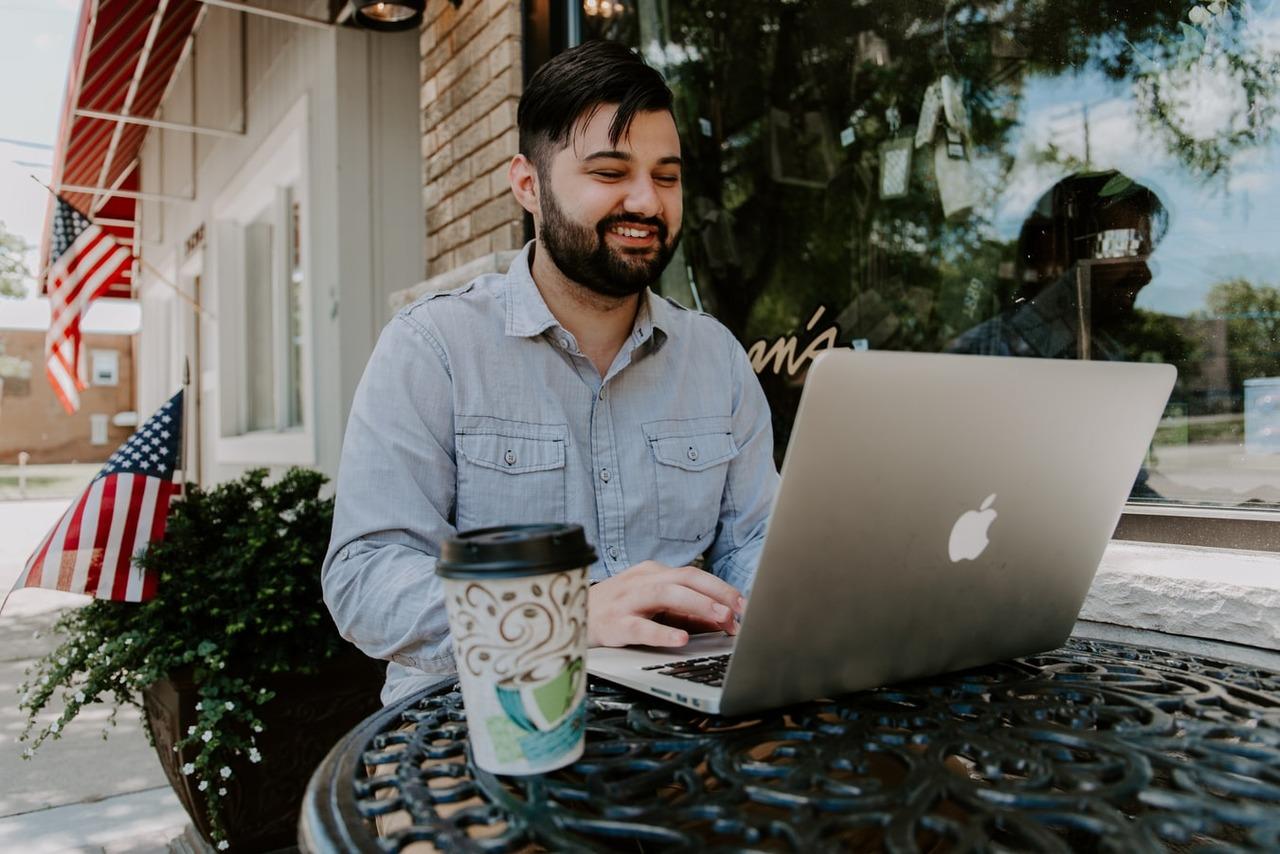Imagem de um rapaz mexendo no notebook, com um copo de café ao seu lado