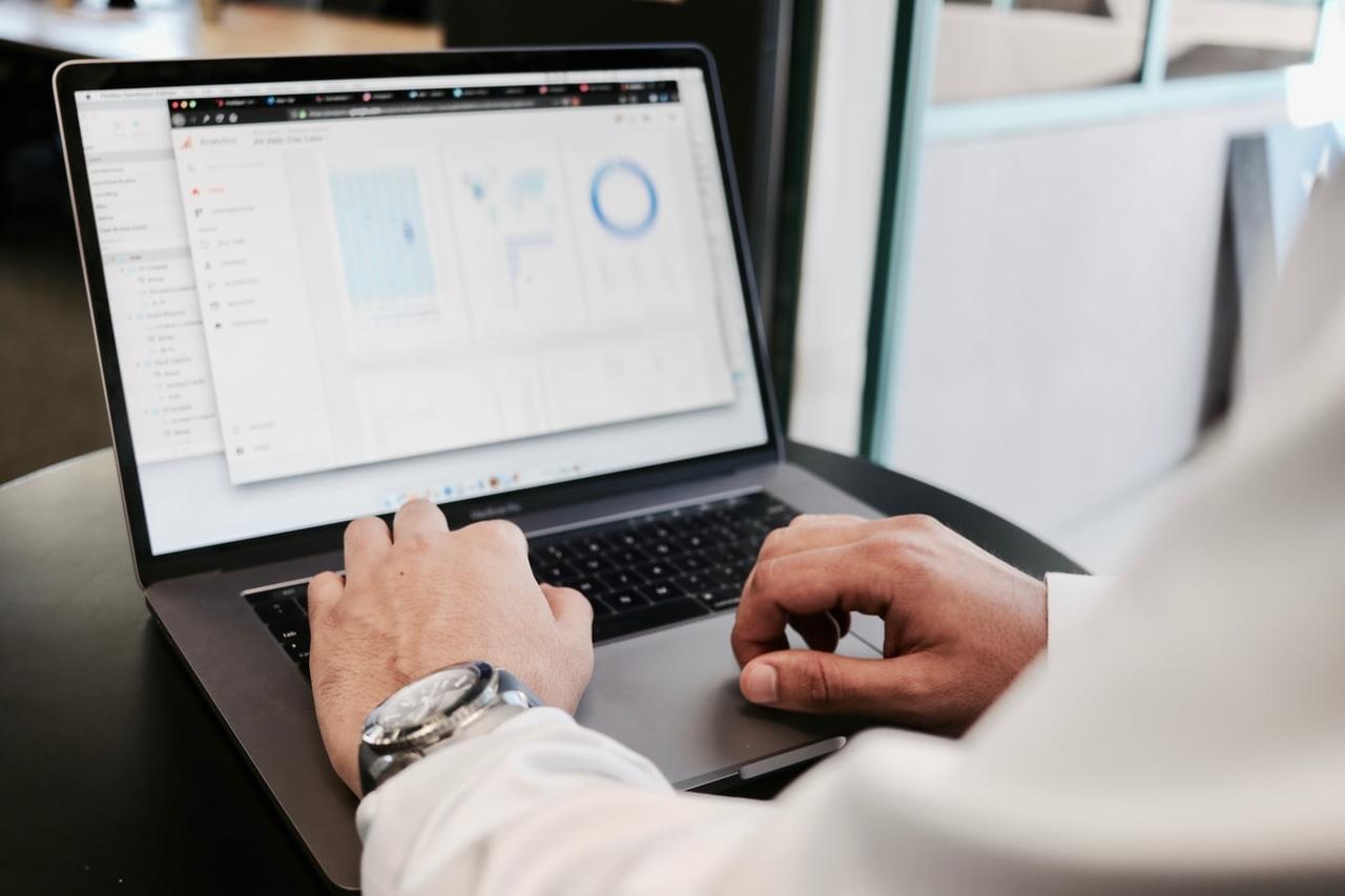 Imagem de um homem de terno mexendo em seu computador