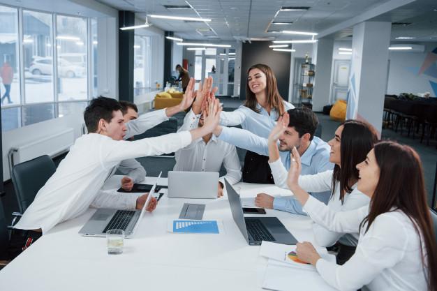 Um grupo de pessoas no trabalho, em uma sala de reuniões, batendo as mãos um dos outros de forma a comemorar bons resultados. A motivação é um dos pilares da comunicação corporativa