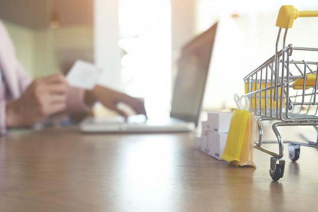 Imagem com um carrinho de compras em miniatura em cima de uma mesa, com pacotes de presente em miniaturas ao lado do carrinho