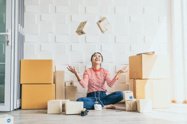 Imagem de uma mulher sentada no chão, com as pernas cruzadas, ela tem caixas de papelão ao seu redor em tamanhos variados, ela joga para o alto duas caixas pequenas