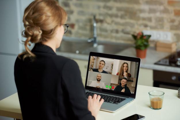 Imagem de uma mulher em uma reunião online, representando a comunicação corporativa
