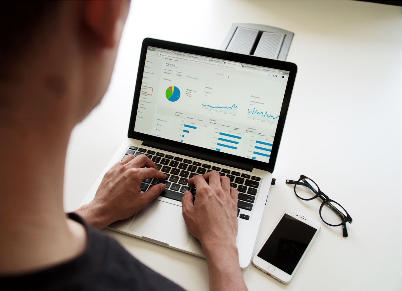 Imagem de uma pessoa sentada à mesa, mexendo em um notebook, com o celular o óculos ao lado direito. Na tela do computador aparece o data driven marketing