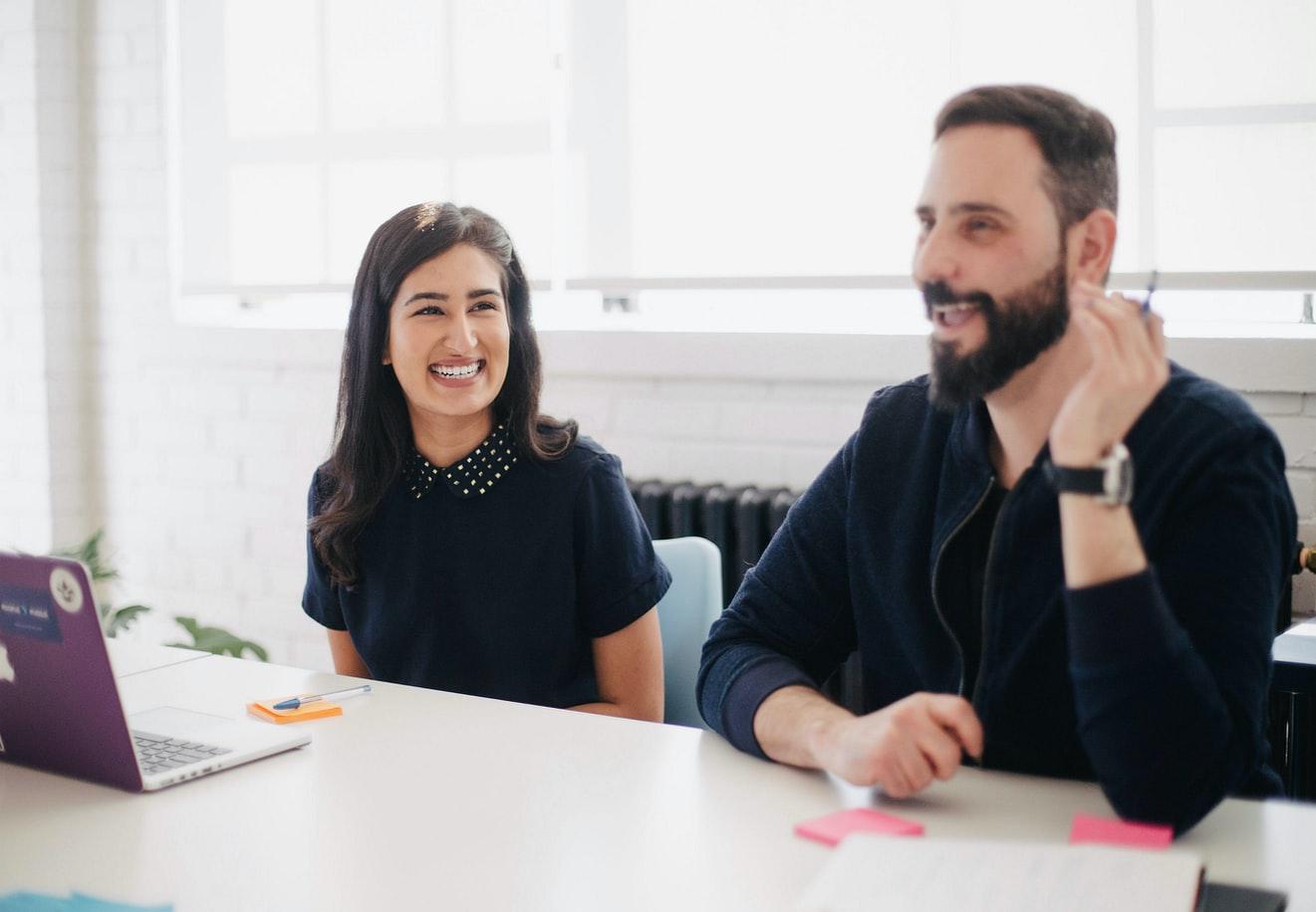 Imagem de uma mulher e um homem sentados à mesa, com computadores abertos, discutindo sobre como identificar um mql