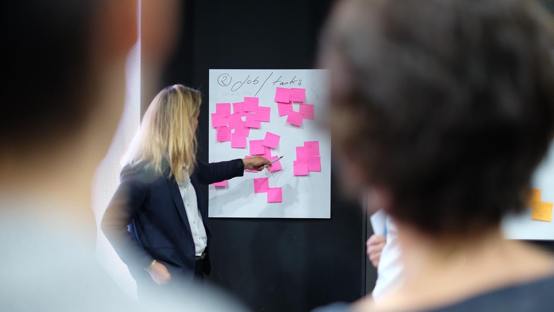 Imagem de uma equipe de marketing, discutindo sobre mql. Há um quadro ao fundo com post it, demarcando a estratégia