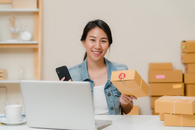 Imagem de uma mulher sentada à mesa com um computador em sua frente e caixas de papelão do seu lado esquerdo. Ela segura uma das caixas retangulares, com uma letra A na lateral e sorri, enquanto segura um celular com a outra mão
