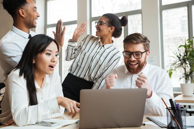 Imagem de uma equipe com especialista em project management comemorando bons resultados
