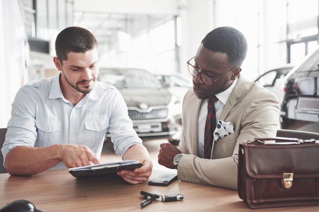 Imagem de dois homens sentados à mesa, um deles vende um carro e o outro compra