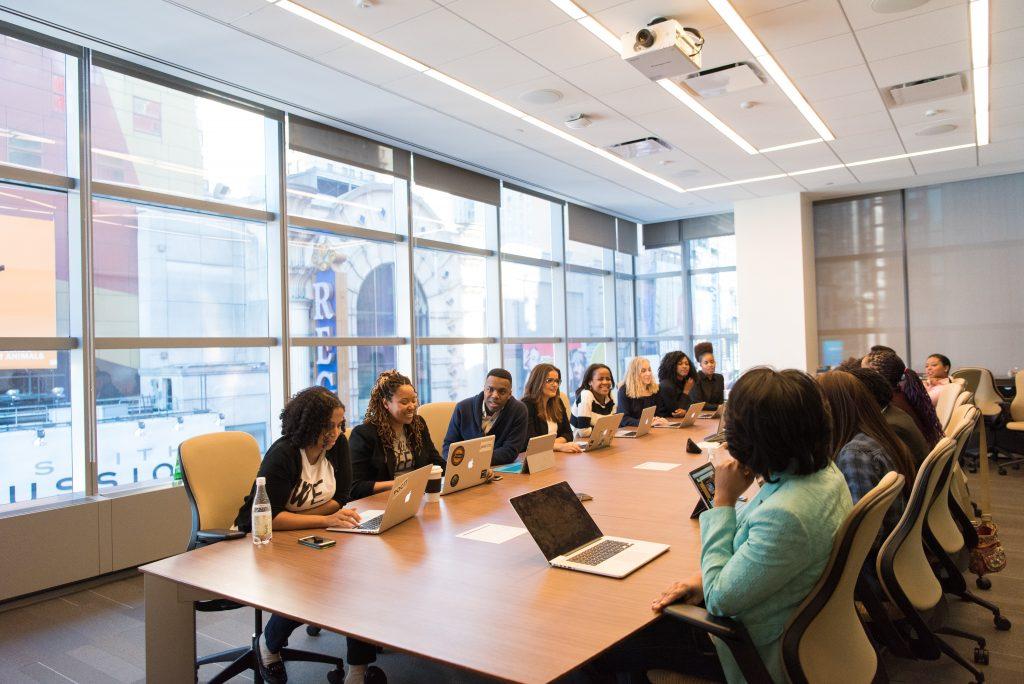 Imagem de uma sala de reuniões com mulheres sentadas à mesa, discutindo sobre algo