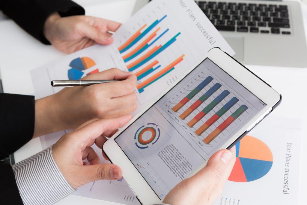 imagem de duas pessoas segurando papéis com dados sobre a transformação digital nas empresas