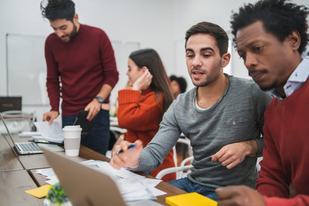 Imagem de uma equipe de inside sales, no centro há dois homens, um negro e outro branco, eles conversam sobre algo e apontam para a tela do computador. Ao fundo uma mulher branco e um homem branco conversam