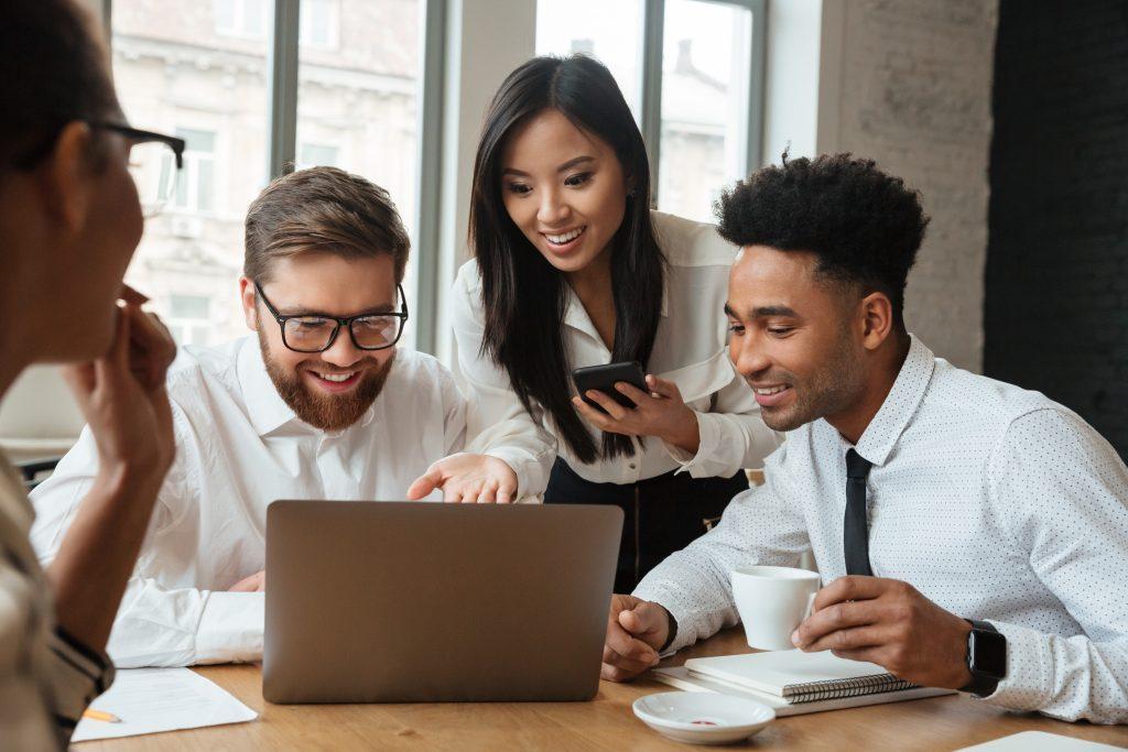Imagem de uma equipe de whatsapp marketing olhando para um computador