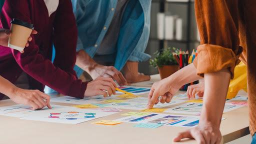 Pessoas em volta de uma mesa, apontando para projetos