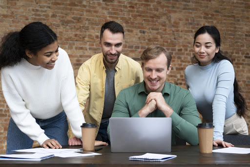 Imagem mostra pessoas olhando para um notebook posicionado em uma mesa
