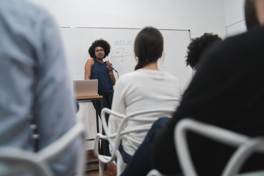 Imagem de uma mulher na frente de pessoas, segurando um microfone e apresentando dados sobre gestão de marca