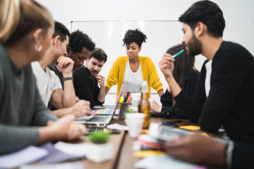 Imagem de pessoas reunidas em um escritório, com uma mulher na liderança