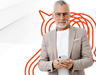 Empresário, de barba e cabelo branco, com celular na mão aproveitando as vantagens de investir em valor de marca.